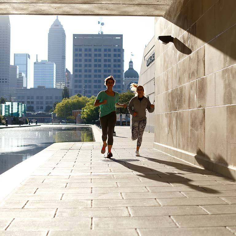 Two people jogging under a bridge along the canal in downtown Indianapolis.
