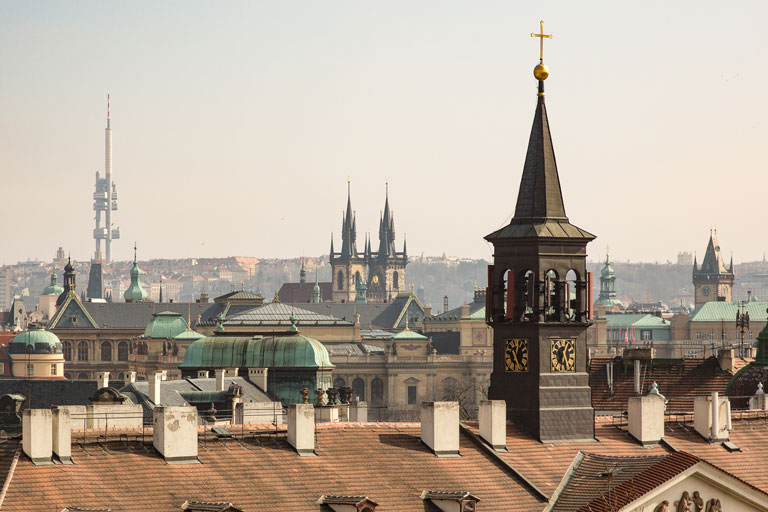 Historic Prague skyline with a large cathedral spire at the center.