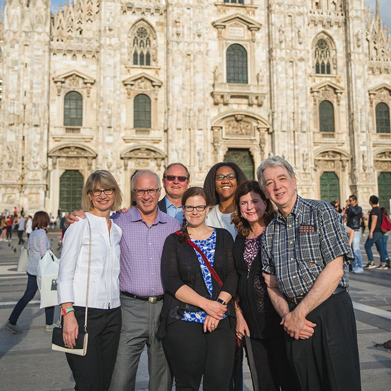 A group of Physician MBA students stand in front of an ornate cathedral in Italy.