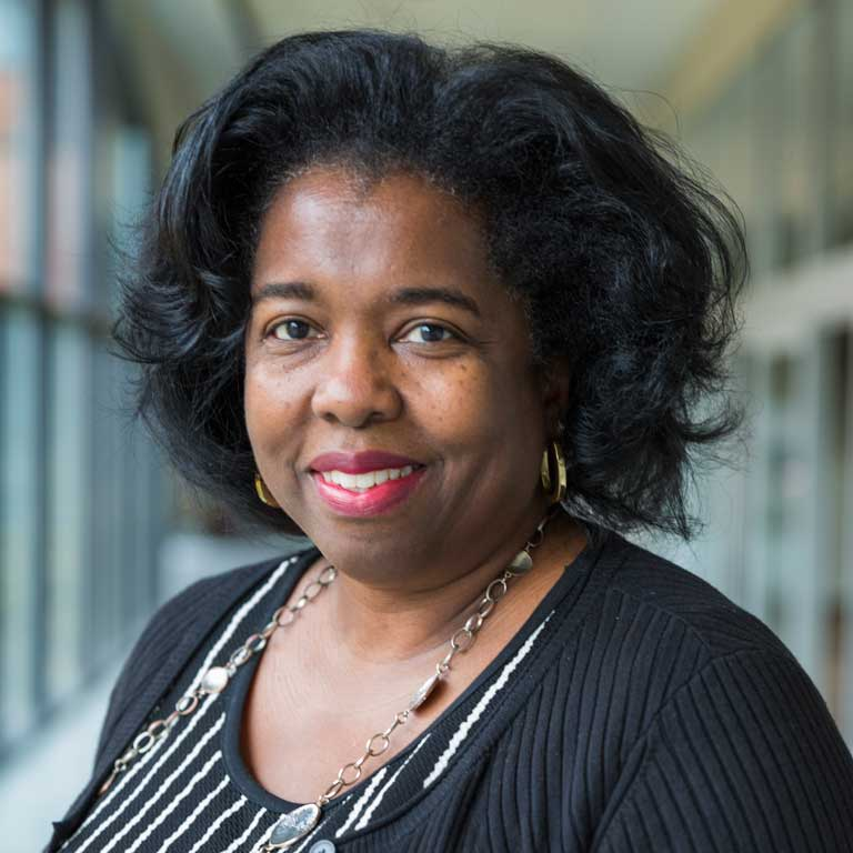 Kelley Physician MBA alumna Dr.Cheryl Wolfe standing in Hine Hall at IUPUI.