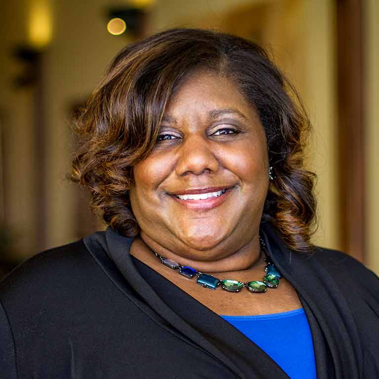 Kelley Physician MBA alumna Dr. Cameual Wright standing in a room smiling.